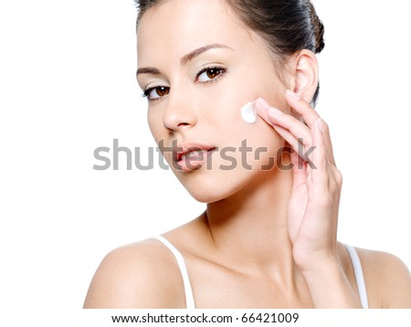 Beautiful woman with sensual look applying cream on her clean face - white background - stock photo