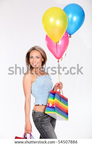Beautiful woman with shopping bags and color balloons - stock photo