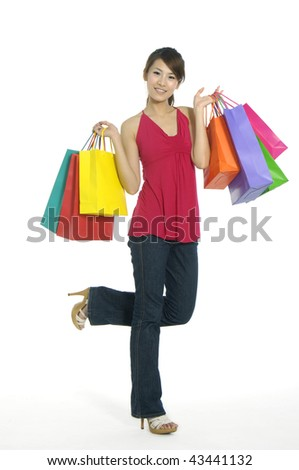 beautiful woman with shopping bags in hand standing in the studio - stock photo