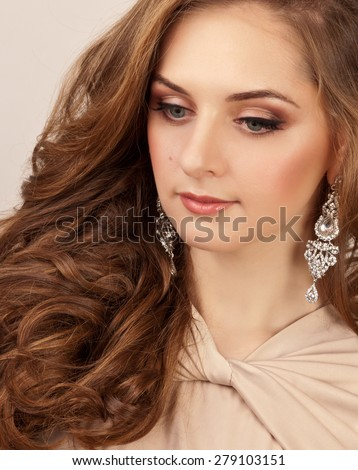Beautiful woman with silver earrings and makeup looking down - stock photo
