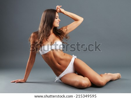 Beautiful woman with slim body in swimsuit on gray background - stock photo