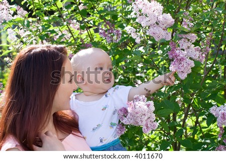 Beautiful woman with small kid and flowers - stock photo