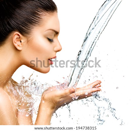 Beautiful Woman with splashes of water in her hands. Beautiful Smiling model girl under splash of water with fresh skin over blue background. Skin care Cleansing and moisturizing concept. Beauty face - stock photo