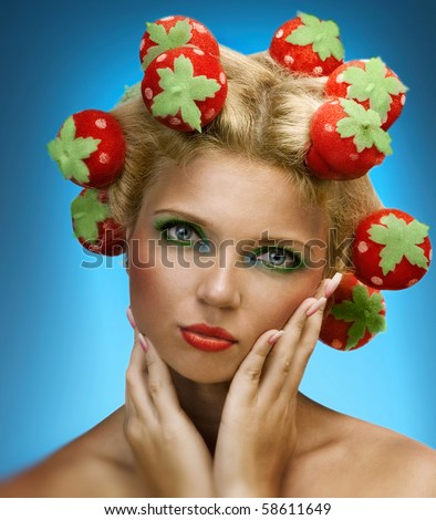 Beautiful woman with strawberries rollers in the hair - stock photo