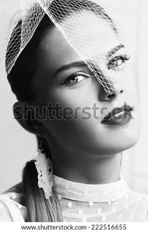 Beautiful woman with stylish hat and elegant white dotted blouse looking forward. Hair style. High fashion model. Portrait of young woman. Beautiful lady. Black and white