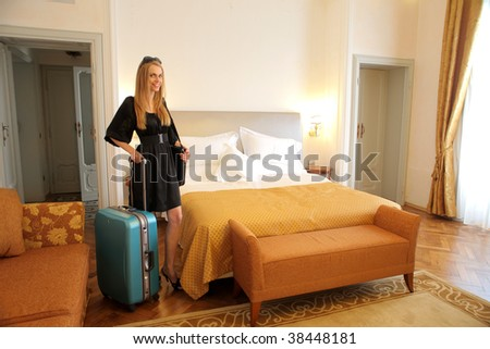 beautiful woman with suitcase in a hotel bedroom - stock photo