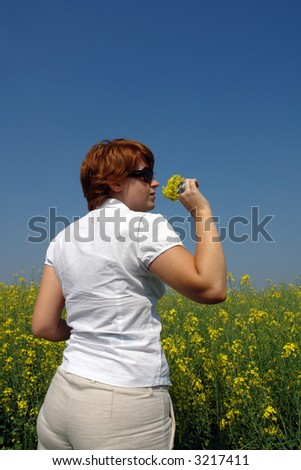 Beautiful woman with sunglasses smelling flowers and visibly enjoying it