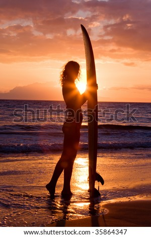 beautiful woman with surfboard standing at tropical sunset - stock photo