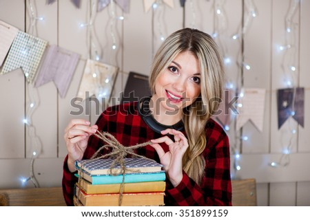 Beautiful woman with the collection of books on a white background wooden wall
