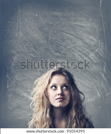 Beautiful woman with thoughtful expression and blackboard in the background - stock photo