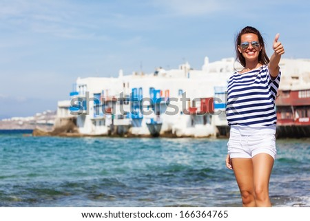 Beautiful woman with thumb up smiling and looking at camera beside the sea - stock photo
