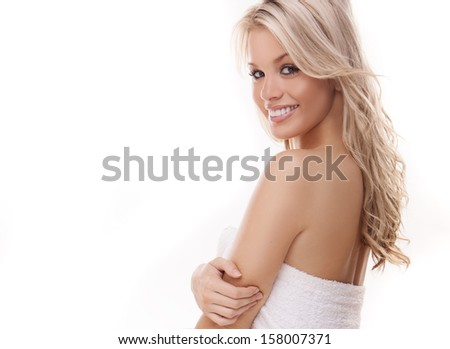 Beautiful woman with tousled blond hair standing sideways looking over her shoulder at the camera with a gorgeous smile, isolated on white - stock photo