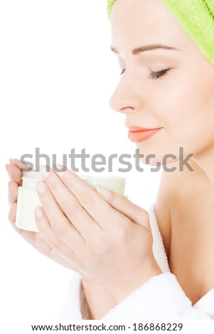 Beautiful woman with towel and in bathrobe with body lotion. Spa concept. Isolated on white. - stock photo
