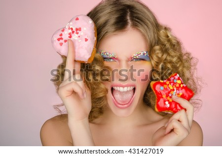 beautiful woman with two donuts on pink background