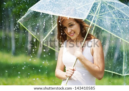 Beautiful woman with umbrella during the rain    - stock photo