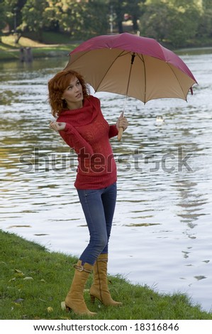 beautiful woman with umbrella looking up the sky if stop raining