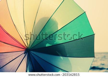 beautiful woman with umbrella on seaside - stock photo
