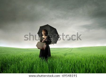 Beautiful woman with umbrella standing on a green meadow