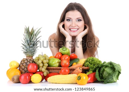 Beautiful woman with vegetables and fruits on table isolated on white - stock photo