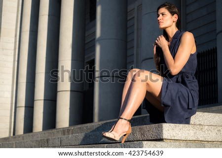 Beautiful woman with very nice legs tearing her hair out alone in a melancholy way - stock photo