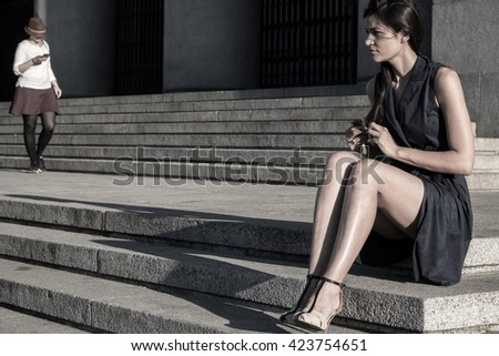 Beautiful woman with very nice legs tearing her hair out feeling alone - stock photo