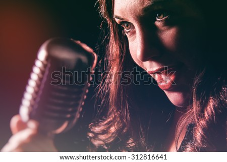 Beautiful Woman with Vintage Microphone. Attractive female singing into a vintage microphone. Set in dark room with spot lighting and edited with vintage effects. - stock photo