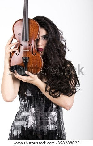 beautiful woman with violin posing with it in front and middle of her face looking at camera
