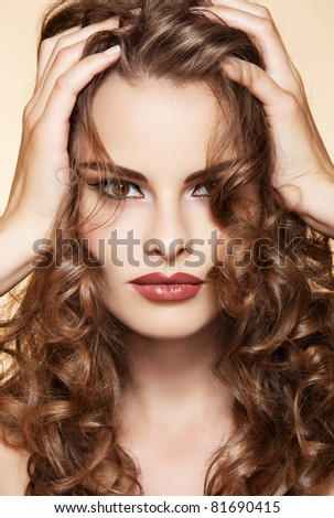Beautiful woman with volume and shiny curly hair style, bright lips make-up - stock photo