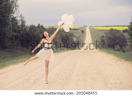 beautiful woman with white balloons outside - stock photo