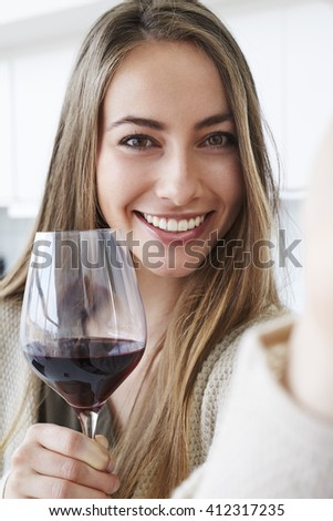 Beautiful woman with wine smiling at camera