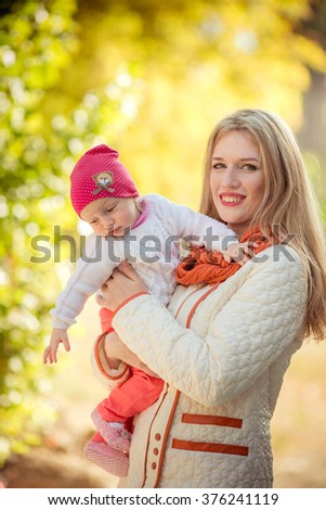 Beautiful woman with young daughter in green garden