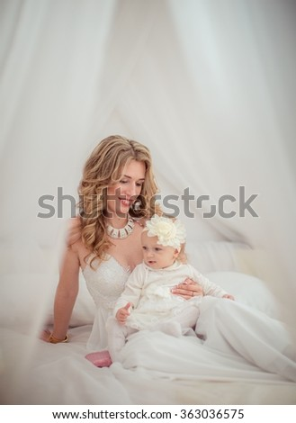 Beautiful woman with young daughter in white dress