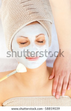 Beautiful woman woman receiving white cream on her face in a spa center