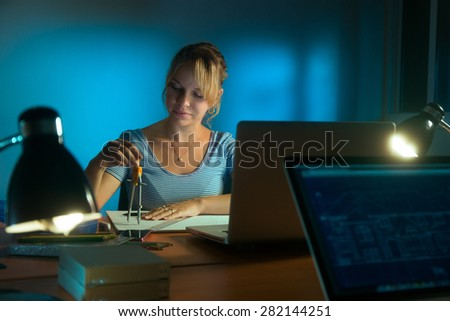 Beautiful woman working as interior designer, staying late at night in office with drawings and laptop computer to complete a project. The girl draws a circle with compasses - stock photo