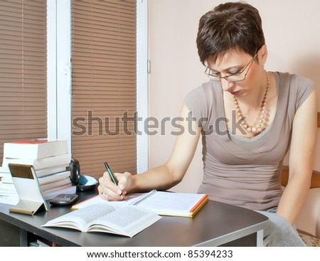 Beautiful woman working at home on agenda