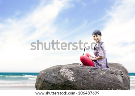 Beautiful woman working on laptop at the beach. shot outdoor - stock photo