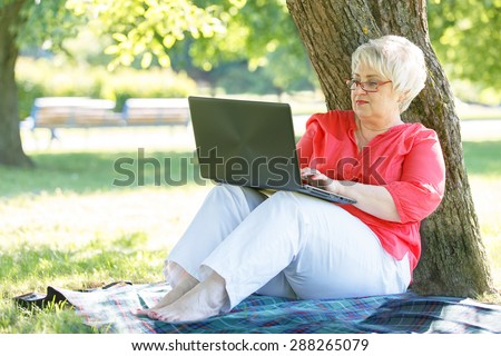 Beautiful woman working on laptop in city park. - stock photo