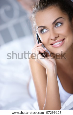 Beautiful woman working on laptop on white bed - stock photo