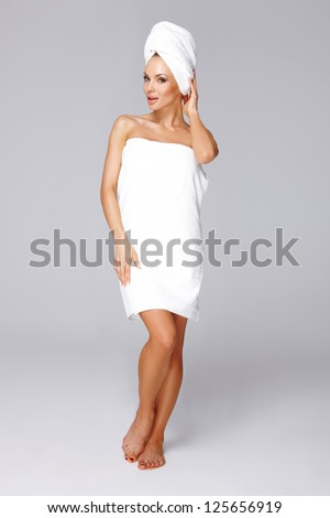 Beautiful woman wrapped in a fresh white towel around her body and hair posing barefoot, full length isolated studio portrait - stock photo