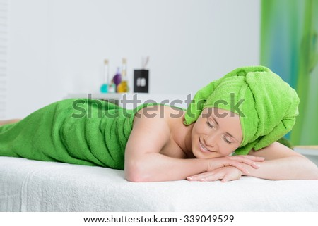 beautiful woman wrapped in green towel in spa salon