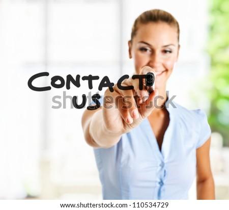 "Beautiful woman writing ""Contact us"" on the screen - stock photo"
