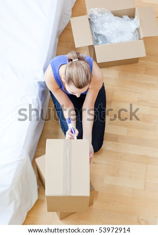 Beautiful woman writing on a box at home