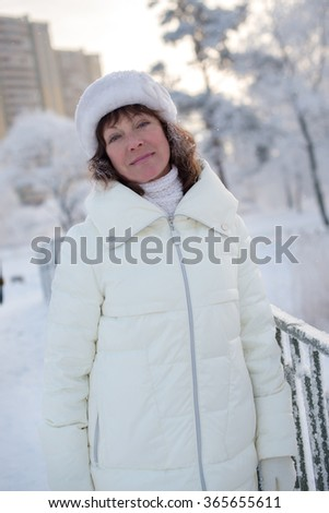 Beautiful woman 50 years old walking on the snowy city of St. Petersburg