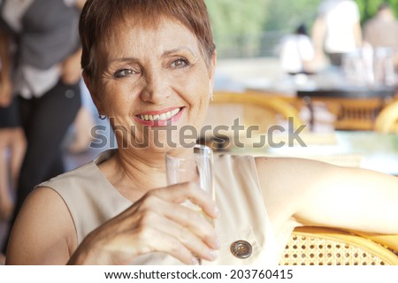 beautiful woman 50 years old with a glass in cafe - stock photo