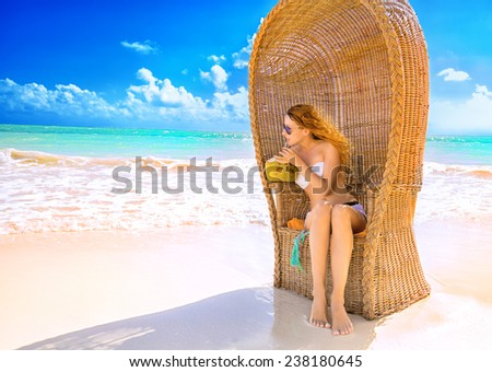 Beautiful woman young lady with sunglasses relaxing on the tropical beach enjoying sea view drinking coconut juice. Freedom travel vacation outdoors lifestyle leisure wellness concept  - stock photo