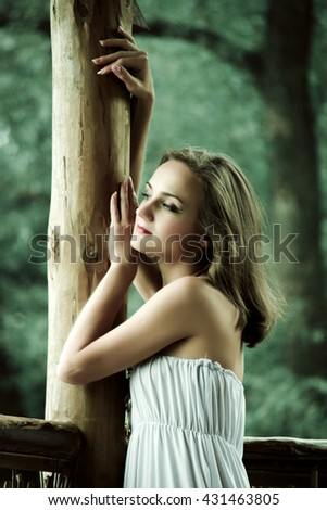 Beautiful woman. Young pretty woman wearing a white dress in a park outdoors. Spring and summer natural beauty concept.