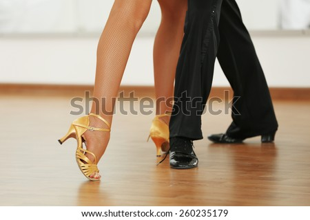 Beautiful womanish and masculine legs in active ballroom dance, indoors - stock photo