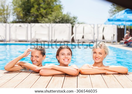 Beautiful women are standing in swimming pool and resting. They are leaning on the board with their hands. The ladies are looking at the camera and laughing - stock photo