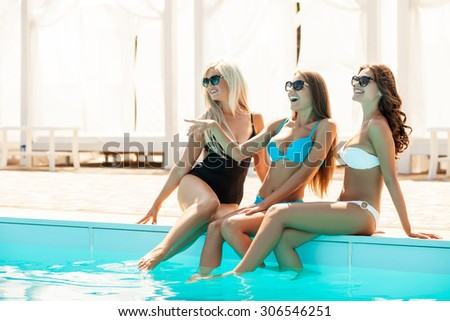 Beautiful women are sunbathing and relaxing. They are sitting and putting their legs into a swimming pool. The brunette lady is pointing finger sideways. They are looking there and laughing - stock photo