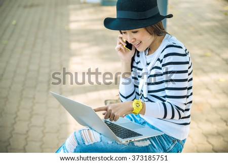 Beautiful women are using a laptop and talking on the phone. in a train station - stock photo